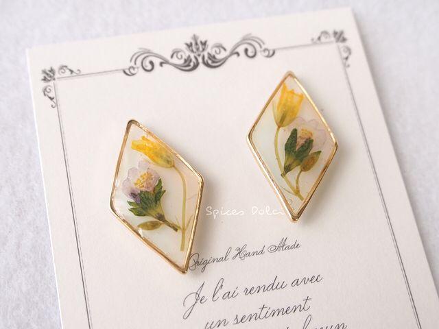 淡い青と黄色のお花とミルキーなホワイトのベースカラーが、ふんわりと優しい雰囲気のピアス(イヤリング)です。フェミニンなお洋服はもちろん、ダイヤ形のゴールドフレームが甘すぎず、カジュアルなお洋服や和装にも合わせて頂けます。<素材/サイズ> ・素材:押し花/...