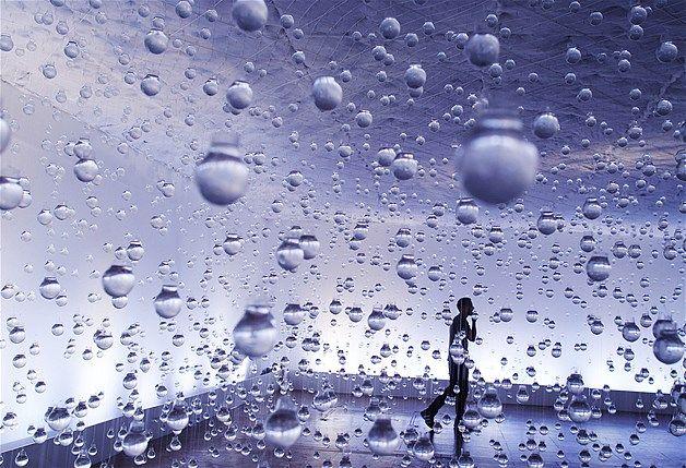 A man walks among light bulbs filled with water as part of the 'Lagrimas de Sao Pedro' exhibit by Brazilian artist Vinicius Silva in Rio de Janeiro.