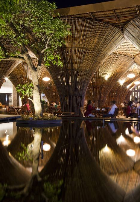 Fifteen conical bamboo columns support the roof of this waterside cafe designed by Vo Trong Nghia Architects at a hotel in central Vietnam