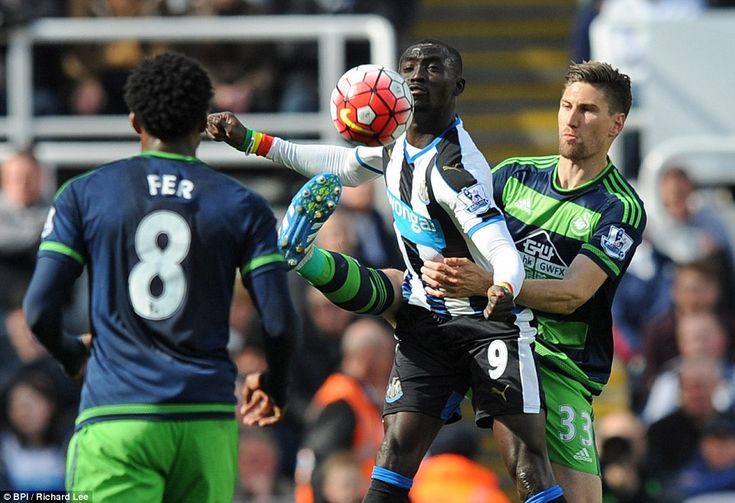 Federico Fernandez of Swansea (right) uses unorthodox means to try and take the ball from Newcastle striker Papiss Cisse (centre)