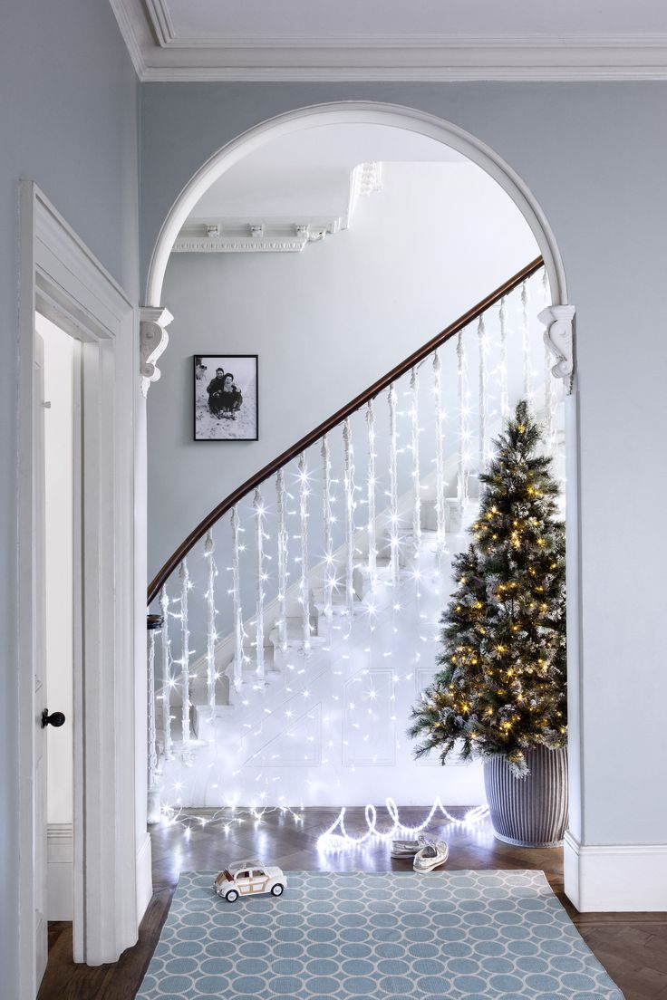 A lovely idea for the bannister is to use icicle lights so each light falls over each of the spindles and down onto the floor. From afar they resemble snowflakes and help to add a bit of wonder to your staircase || Image Credit: Lights4fun | Styling: Lucy Gough | Photography: Oliver Perrott