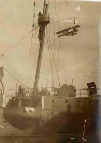 3 officiers prennent la pose sur le pont, tandis que la vigie est survolée par un hydravion.  (Photo d'un hydravion survolant le pont d'un navire de guerre)