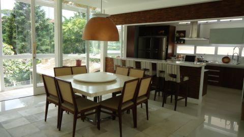 Projetada pela arquiteta Grace Srulzon, esta sala de jantar fica em São Paulo e se beneficia da luz natural. O balcão comprido tem tampo de silestone branco, que se destaca na parede de mosaico de madeira. A mesa de madrepérola é rodeada por cadeiras com encosto de palhinha.