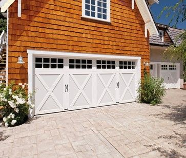 Clopay Coachman Collection steel carriage house style garage doors, Design 21, SQ24 windows in white with standard spade lift handles. The detached garage has living space above so insulation and quiet operation are important considerations.
