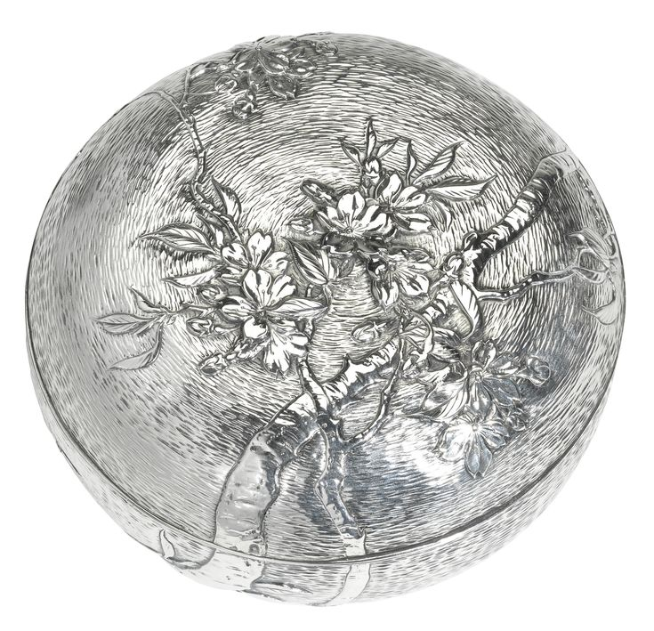 A Japanese Meiji period silver box and cover, Kuhn & Komor, Yokohama, circa 1900 the double-skinned cover and body embossed in relief with a climbing cherry blossom tree on a textured ground