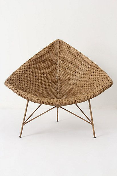 "Naida Chair: ""A juxtaposition of modern and natural, this sleek silhouette of hand-woven wicker stands atop spindly steel legs."""