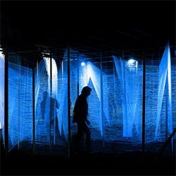 Lasermaze by George King Architects is an architectural installation formed from three miles of UV wool and over 3000 hand tied knots, suspended from an industrial structure of steel scaffolding and chains.