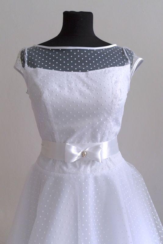 Puntíkaté svatební šaty Krátké šaty z puntíkatého tylu. Kolová sukně ke kolenům, podložená několika vrstami tylu a taftem. Na podšívce tylový volán. Krátké rukávky. Vzadu zip, příp. i knoflíčky. V pase saténová stuha s mašlí a broží. Velikost dle přání, nejlépe na míru. Tyto šaty jsou ve vel. 38,