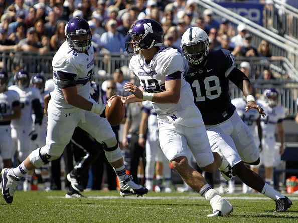 Trevor Siemian Photos Photos - Trevor Siemian #13 of the Northwestern Wildcats is hurried by Deion Barnes #18 of the Penn State Nittany Lions in the first half during the game on September 27, 2014 at Beaver Stadium in State College, Pennsylvania. - Northwestern v Penn State