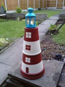 Terra Cotta Lighthouse-2 large plant pots cemented together and painted,with a lantern on top.