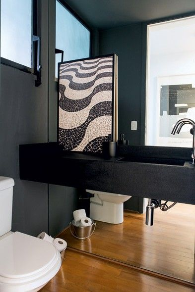 No lavabo, um baldinho de metal organiza os rolos de papel higiênico. O espelho embaixo da bancada amplia o ambiente. Quadro com foto feita pelo morador, o empresário Chico Paese