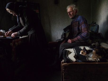 """A great picture taken in a remote village of Maramureș - Northern Transylvania has been awarded with """"honorable mention"""" by National Geographic at the Photo Contest 2014. http://on.natgeo.com/1z8WN4H  The author is Roberto Fiore.   The caption stands as follows: """"he was waiting on the bed, lost in thoughts, while his wife was preparing the bread to be blessed for the orthodox Eucharist."""""""