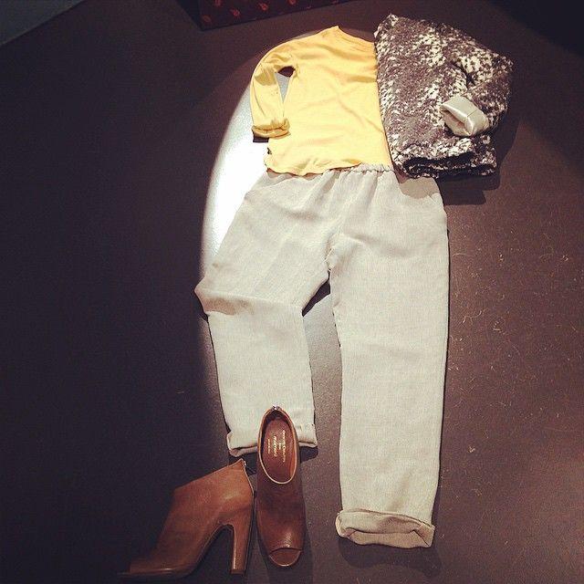 Stivaletti camoscio, pantaloni bianche o culotte grigi, maglia gialla, cappotto  lungo o cappa.