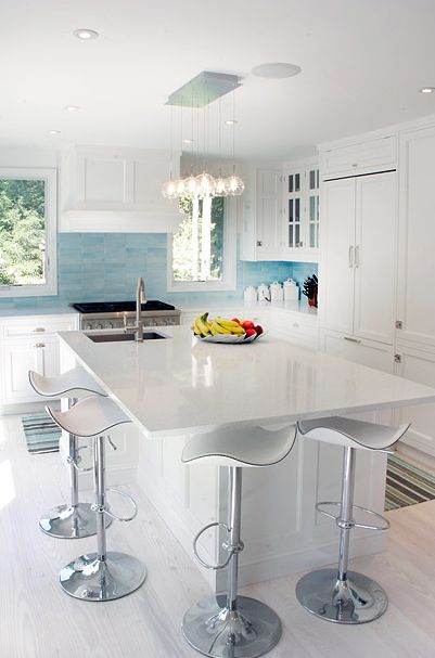 Elsa Soyars    white & turquoise blue contemporary kitchen design with white modern kitchen with white cabinets, blue glass tiles backsplash, striped blue green brown rug, kitchen island, marble countertops, modern counterstools and pendant lighting.