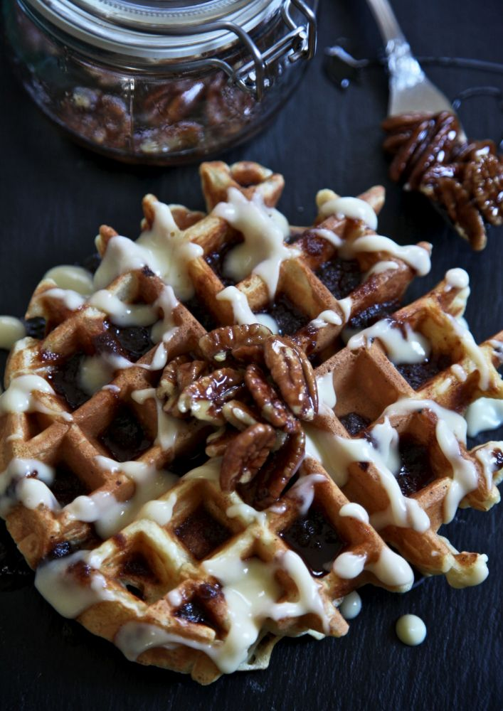 Hot buttermilk waffles are drenched in brown sugar, cinnamon and butter syrup with tangy cream cheese icing drizzled over and sprinkled with toasted pecans in maple syrup for an extra crunch.