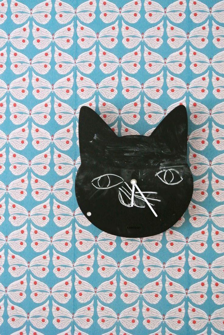 Blackboard clock cat on stunning butterflies wall paper.