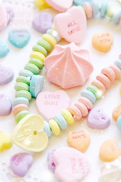 Pastel candies - meringues, conversation hearts, and candy necklace.