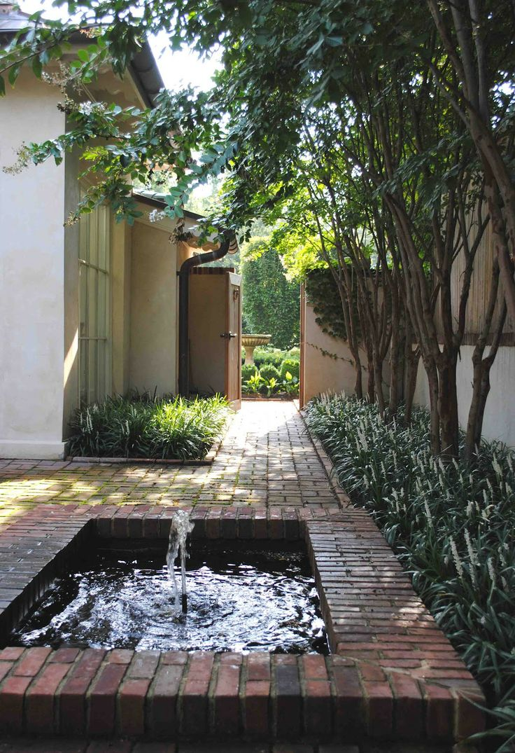Here is our little courtyard garden. We built the fountain and painted it black so it would appear deeper. There are 6 white blooming Natchez crape myrtle trees underplanted with Monroe White liriopes.