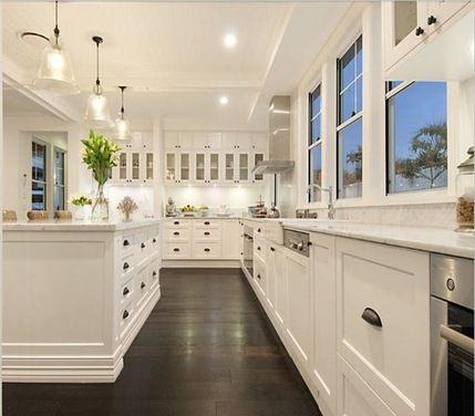 White Farmhouse Kitchen. Farmhouse Charm. Love the dark floors. Love all of the windows.