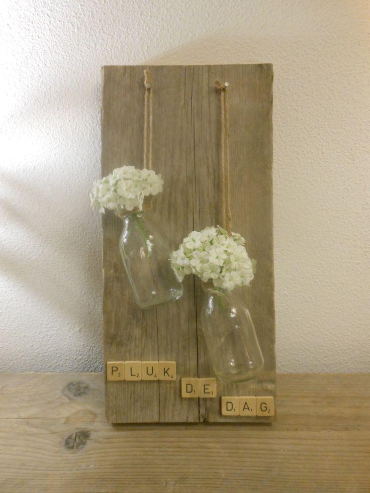 Pluk de dag! Een stuk steigerhout beplakt met scrabbelletters en er boven 2 glazen flesjes aan touw opgehangen.Leuk om kleine bloemetjes in te doen.Ook leuk voor aan de schutting.