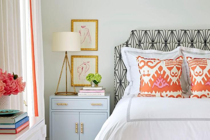 Chic teenage girl's bedroom features a gray and black headboard upholstered in Kelly Wearstler Katana Fabric on bed dressed in platinum gray border bedding as well as orange ikat pillows in Quadrille Kazak Coral New Yellow on Tint on Suncloth situated next to a gray nightstand with gold bamboo pulls, Worlds Away Marcus Grey Cabinet, as well as a gold lamp, Fontaine Table Lamp, placed under pink abstract nude sketches in gold picture frames.