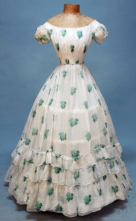 Young lady's summer party dress. 1860s. White cotton voile with horizontal pinstripe weave printed with shaded green oak leaves.  Drawstring at neckline. Cotton lining (bodice) with back hooks and eyes.