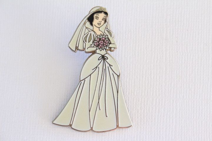 This gorgeous rare Disney Pin for sale features Princess Snow White and the Seven Dwarfs Bride on her Wedding Day. She is wearing a beautiful white pearly wedding dress holding a pink bouquet of flowe