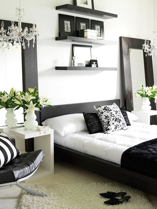 Black and White All Over is a poplular contemporary decorating trend. This b duo is both flirty and sophisticated.  2 floor length mirrors complement the black wood framed bed and highlight two glass chandeliers.  Above the bed, three floating shelves allow for space to display photos or other fav accessories.
