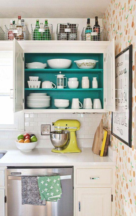 Organization Inspiration: Tidy Kitchens. Color hides inside the cupboards. Wire baskets corral long-term storage items above the low-hung cupboards.: