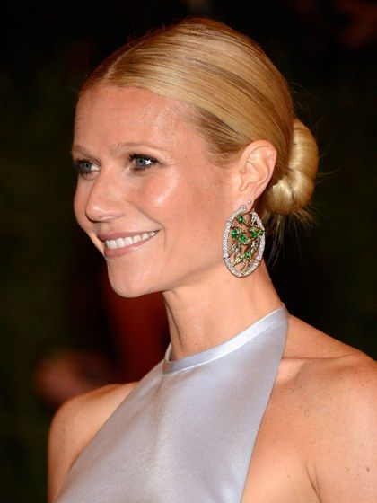 Gwyneth Paltrow Paltrow's sleek knot is gorgeous for a more formal occasion—not to mention the ideal style to show off a pair of statement earrings. While hair is damp, spray it with Kérastase Reflection Chroma Cristal Shine Perfecting Mist, says hairstylist Bridget Brager. After blowing it dry, part hair in the center and smooth it into a low ponytail. Brager recommends slipping hair into a sock-bun tool, like the Sarah Potempa Wrap Up, which winds hair into a perfectly round shape. Secure…