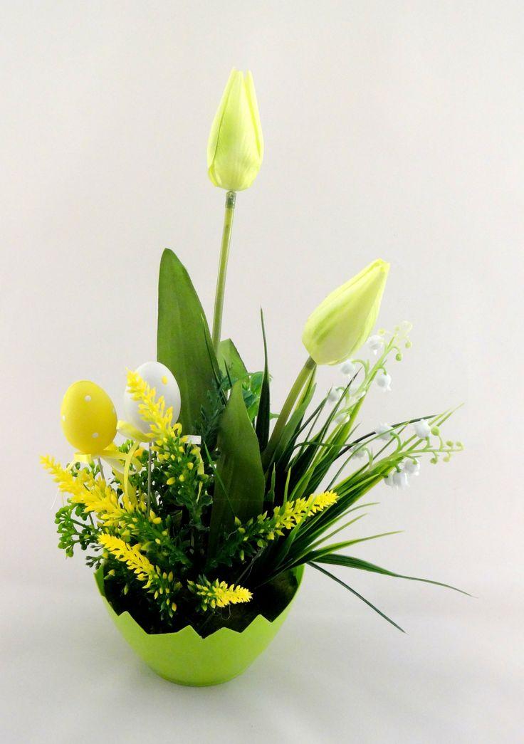www.abgHomeArt.pl Ręcznie wykonany z dbałością o każdy szczegół wielkanocny stroik w zielonej osłonce w kształcie połówki skorupki jajka z kwitnącymi tulipanami i kwiatuszkami w kremowo-zielonej kolorystyce. Udekorowany żółtymi jajeczkami na piku.   Efektowna i radosna wielkanocna dekoracja, która pięknie przyozdobi stół, komodę, czy też kominek, a także wprowadzi powiew wiosny. Idealny do każdego wnętrza.
