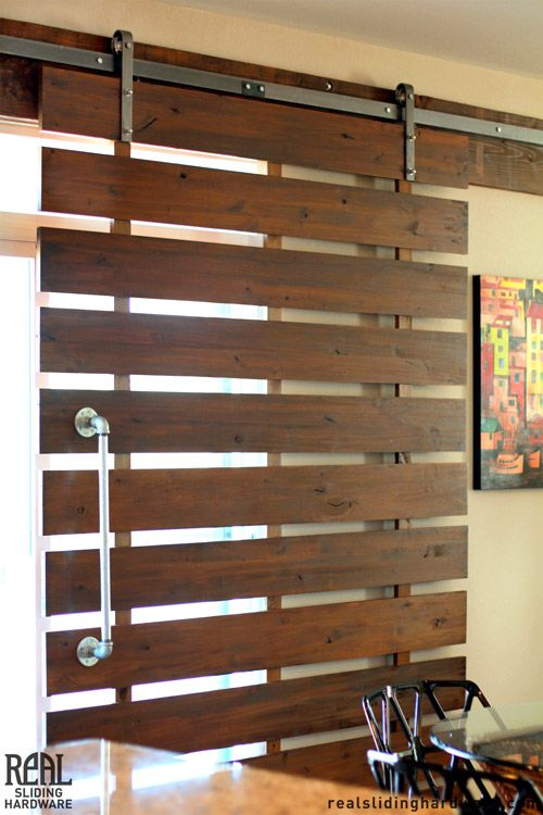 Sun control - Slatted sliding door with barn door hardware.