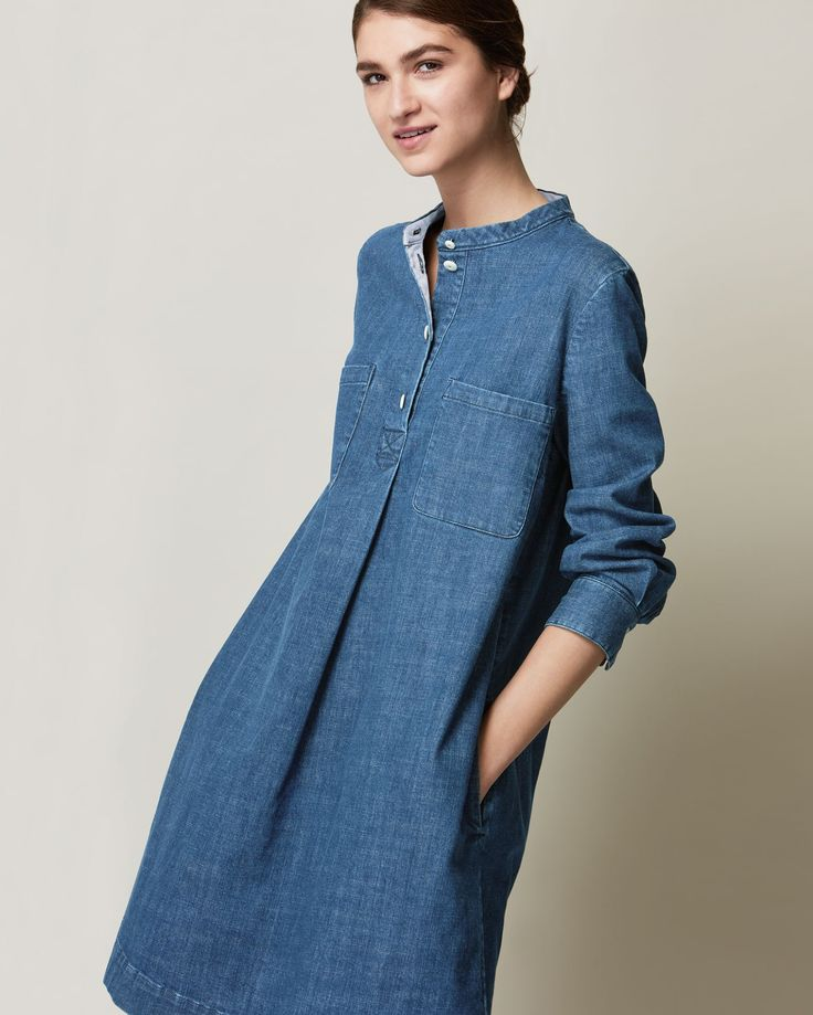 Collarless, slightly A-line dress in a weighty, sturdy but supple, indigo-dyed denim - washed to a slightly softer shade of indigo. Front opening with four corozo shank buttons. Pleat below placket and large box pleat into back yoke - giving a fullness to the shape. Two patch pockets and two in-seam pockets. Bracelet length sleeves with double button cuffs. Cotton facing at neck, cuffs and pockets - shown when the cuffs are worn rolled.