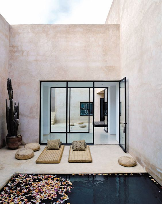 eclectic modern geometric outdoor space with floor seating and flower petals in the pool