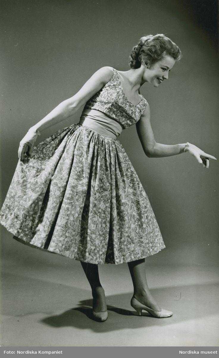 """Brud och Hem, 1957, """"Romans"""". Modell i mönstrad klänning, handskar och pumps. Foto: Erik Holmén för Nordiska Kompaniet"""
