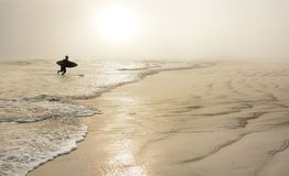 Man  with surfboard on the beautiful foggy beach. Stock Photo