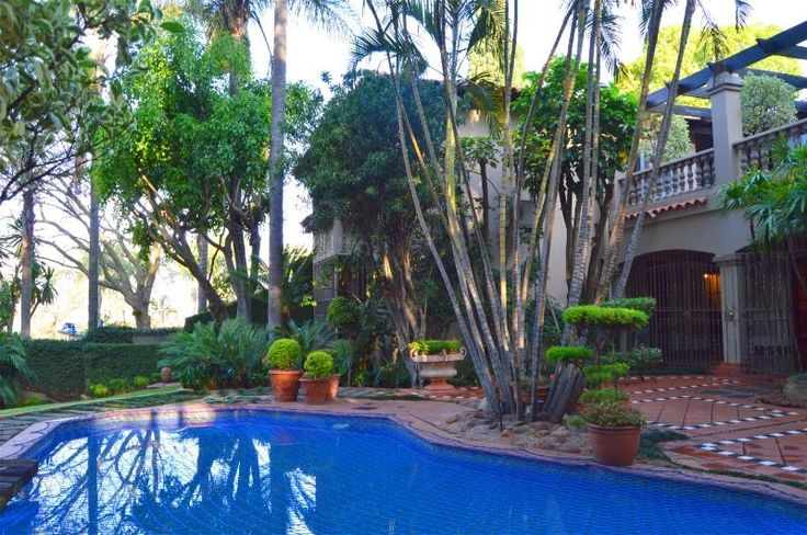 This stunningly appointed Anton Richter designed mansion is situated in Waterkloof in a peaceful treed street with a beautifully landscaped garden & mosaicked pool.  All the bedrooms lead onto a large balcony/patio with a sweeping staircase leading to the pool.