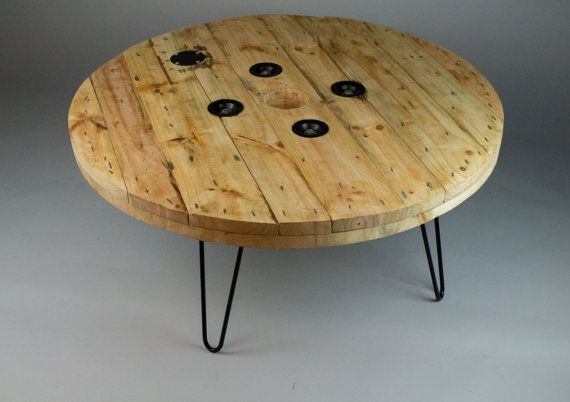 Trenta Reclaimed Cable Reel Coffee Table with Hairpin legs by Timber Bros.  The perfect top for a large room where casual meetings are held or even as a beautiful center piece in any living room. These cable tops come from India and have spent years of hard work traveling continents. Rescued from a steel yard at the shipping ports in Felixstowe and re imagined as a unique and rustic large center piece table top. Coupled with matte black hairpin legs and branded on the underside with the…