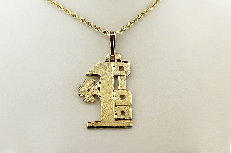 """14kt gold pendant featuring the words """"#1 Дiдo"""" (""""#1 Grandfather"""" in Ukrainian) in block lettering."""