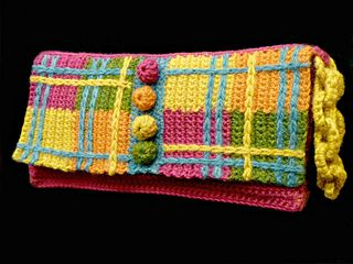 This fun purse was inspired by textile and jewelry elements, and the result is whimsical and elegant. Surface crochet is used to embellish the front flap and transform it into a plaid. Crochet bobble buttons fasten easily and are a unique closure. The chain wrist strap allows you to carry the purse hands free while looking fashionable.