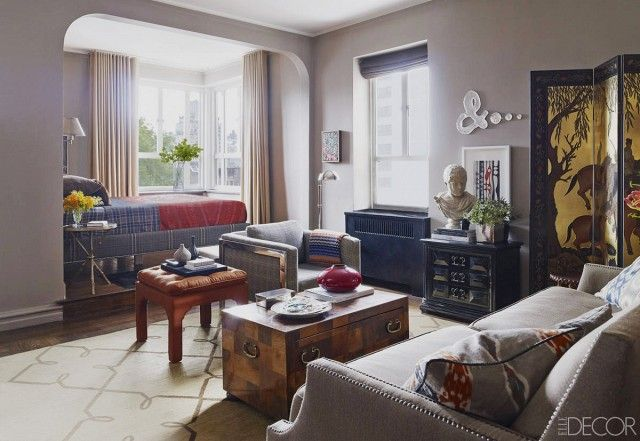 Masculine inspired studio space with a gray sofa, a modern gray tweed armchair, and a vintage trunk coffee table