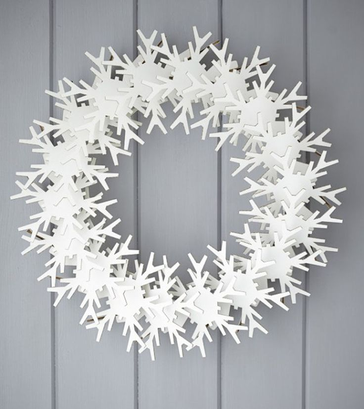 21 Modern Wreaths To Decorate Your Home With This Holiday Season // This modern wreath featuring cardboard snowflakes creates a geometric looking wreath that's both festive and unique.