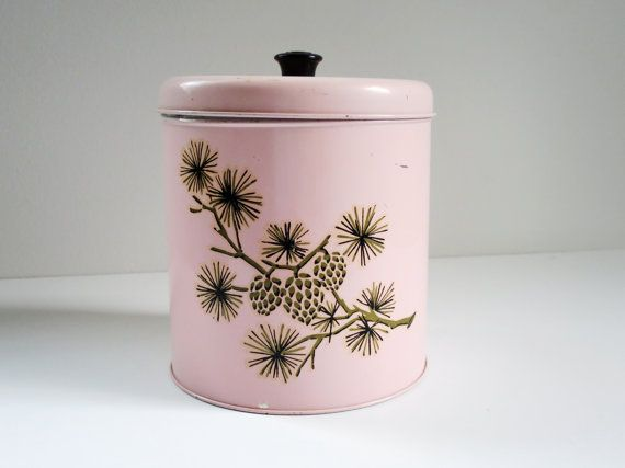 One (1) vintage pink storage tin. A pink tin c. 1960s measuring approximately 7 inches high. This tin does have some minor rusting (see pictures above) so would not be for food storage but could easily store dry goods or used simply as decor. This tin has scuffing and one slight dent on the back where the seam of the tin is. Overall this is in great shape and the minor flaws mentioned above do not in any way distract from its display value or ability to be used.  Please see shipping info…