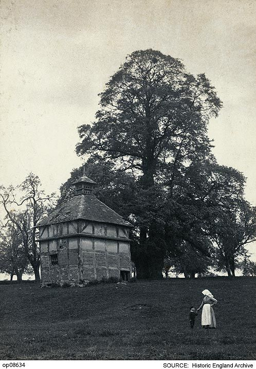 OP08634 View of a half-timbered dovecote at Oddingley, Worcestershire showing a woman and child standing in the foreground  At the time the photograph was taken the dovecote was standing in a field to the south of The Old Farmhouse (Church Cottages) with which it has been associated. In 1930, it was described as dilapidated and has subsequently been demolished.  Date14 May 1894  Photographer: Percy Thomas Deakin   www.Pastscape.org record number 118283