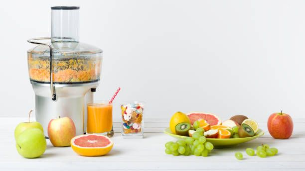 modern electric juicer and fresh oranges white background