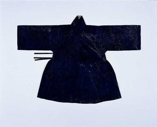 """""""Aekjureum was one of the daily wear for men until the mid-Joseon period. The name itself indicates the gathers under the armpit, and these gathers for the ease of movement is the characteristic of Aekjureum. This double layered Aekjureum is made of dark bluish satin, and lined with off-white silk tabby. It is suggested that the coat was for horse ridings, based on the length different of the front and back panels."""" 16th century. Seok Juseon Memorial Museum, Dankook University."""