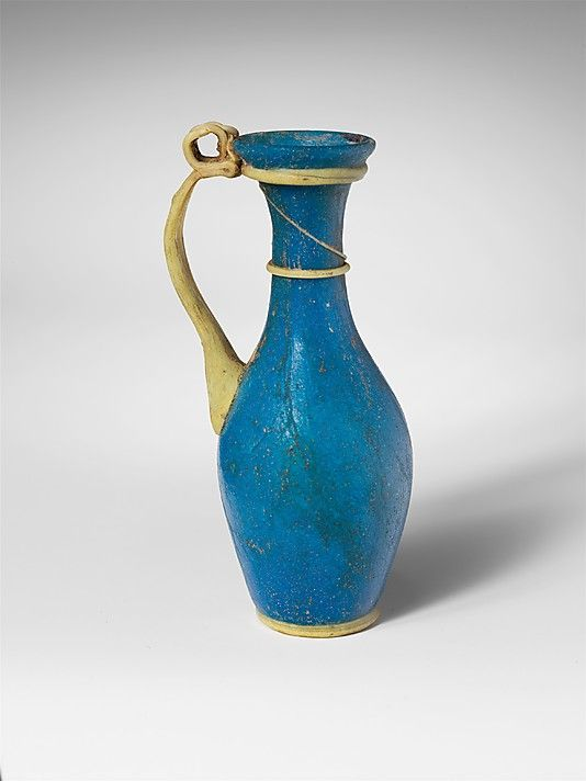 3rd–4th C. Blown translucent deep turquoise blue glass jug with traied and ribbed handle, base in semi-opaque yellow. Roman. MET