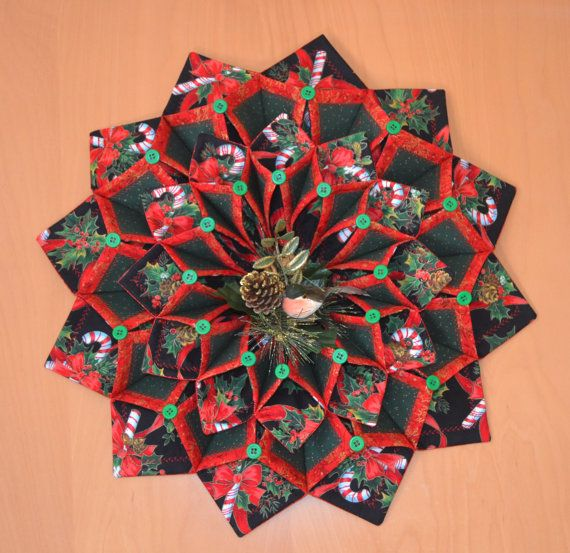 19 foldn stitch wreath. A black with red and white candy canes and green holly Christmas fabric, accented with red and green metallic fabric. Accented with a floral bird pick.