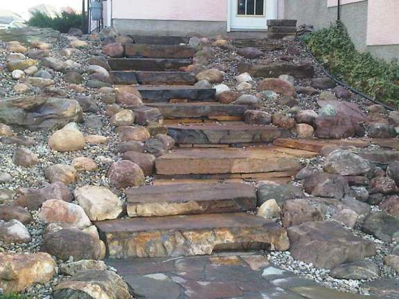 This newly completed project is waiting for shrubs to add some colour. These natural stone steps and rock garden, replaced a steep, slippery, and often muddy hill. Stonework by Dream-yard.