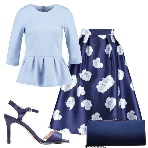 Maglia peplum azzurra con maniche 3/4 e scollo tondo, gonna a campana con sfondo blu scuro e stampa floreale, sandali blu con cinturino alla caviglia, clutch in raso blu con catenella.